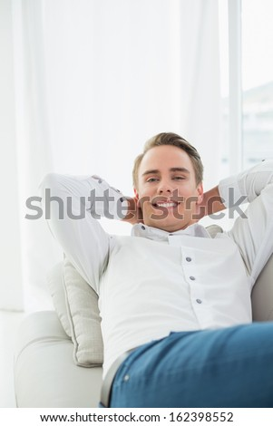 Portrait of a smiling relaxed young man lying on sofa in a bright house
