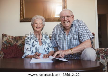 Portrait of a smiling retired couple looking over documents. Senior caucasian man and woman sitting on sofa at old age home and signing some paperwork. - stock photo