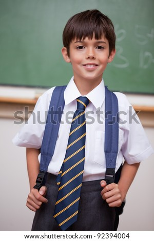 Portrait of a smiling schoolboy with a backpack in a classroom - stock photo