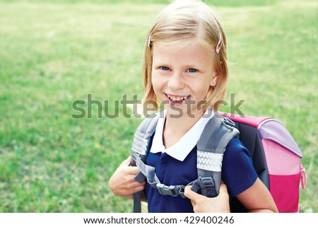 Portrait of a smiling schoolgirl in a blue school dress. The child goes to school - stock photo