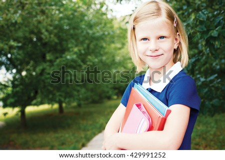 Portrait of a smiling schoolgirl in a blue school dress, with books. - stock photo