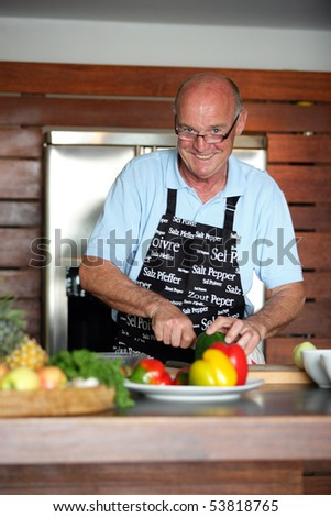 Portrait of a smiling senior man cooking - stock photo