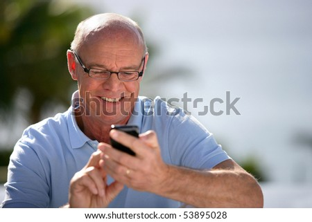 Portrait of a smiling senior man phoning - stock photo