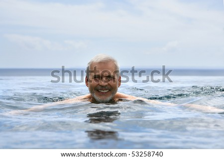 Portrait of a smiling senior man swimming