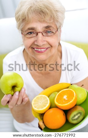 Portrait of a smiling senior woman holding a variety of fruits in her hands - stock photo