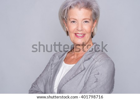 Portrait of a smiling senior woman in front of gray background - stock photo