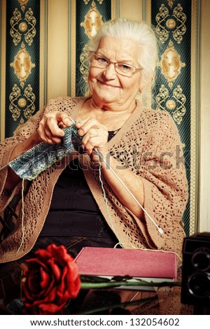Portrait of a smiling senior woman knitting on spokes at home. Old-fashioned style. - stock photo