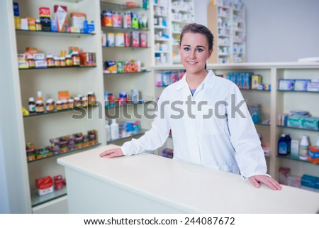Portrait of a smiling student in lab coat looking at camera in the pharmacy - stock photo