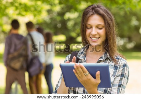 Portrait of a smiling student with a shoulder bag and using tablet computer in park at school - stock photo