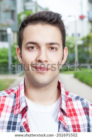 Portrait of a smiling student with checked shirt - stock photo