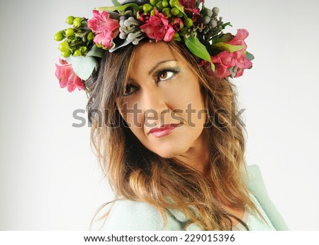 portrait of a smiling tanned beautiful lady with long hair and perfect make up wearing orchid wreath and light mint coat looking down isolated on White background - stock photo