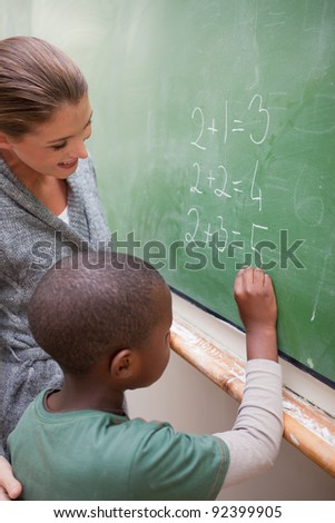 Portrait of a smiling teacher and a pupil making an addition in a classroom - stock photo