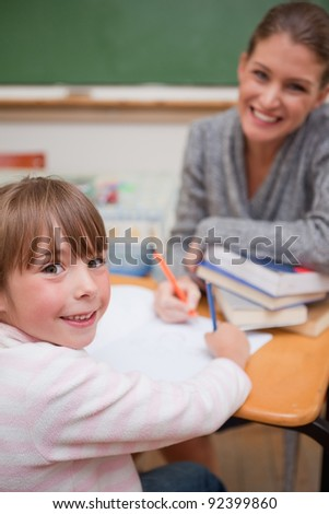 Portrait of a smiling teacher explaining something to her pupil in a classroom - stock photo