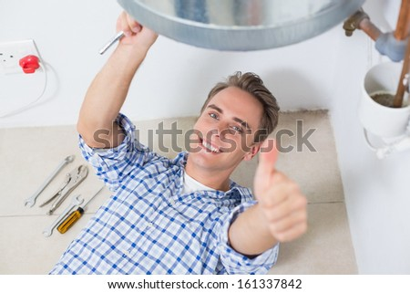 Portrait of a smiling technician gesturing thumbs up by hot water heater