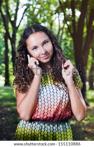 Portrait of a smiling teenage girl with curly hair talking mobile outdoor