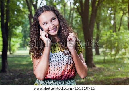 Portrait of a smiling teenage girl with curly hair talking mobile outdoor - stock photo