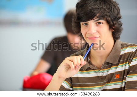 Portrait of a smiling teenager holding a pen - stock photo