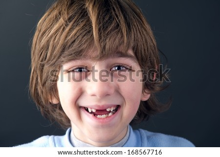 Portrait of a smiling toothless boy - stock photo