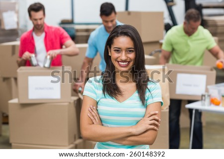 Portrait of a smiling volunteer with arms crossed in a large warehouse - stock photo