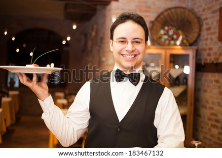 Portrait of a smiling waiter at work - stock photo