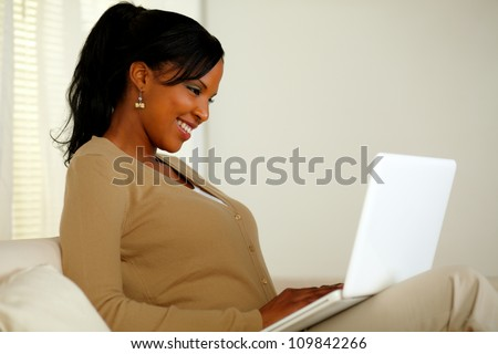 Portrait of a smiling woman browsing the Internet on her laptop while sitting on sofa at home - stock photo