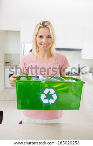 Portrait of a smiling woman carrying recycling container in the kitchen at home