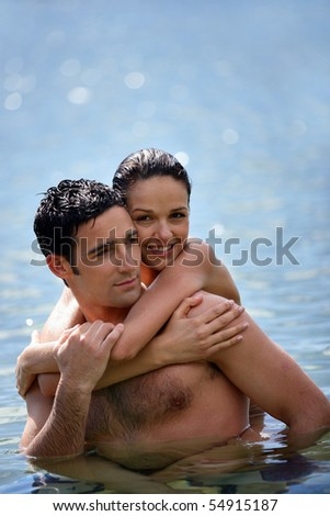 Portrait of a smiling woman embracing a man in the sea