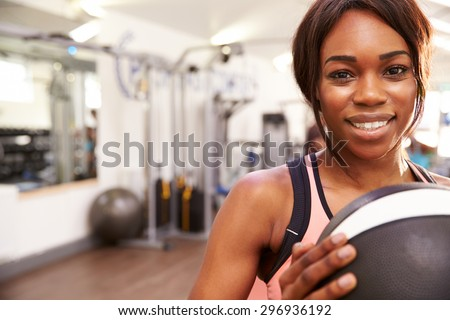 Portrait of a smiling woman holding a medicine ball at a gym, copy space - stock photo