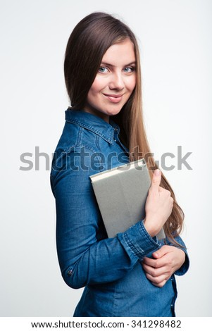 Portrait of a smiling woman holding book and looking at camera isolated on a white background - stock photo