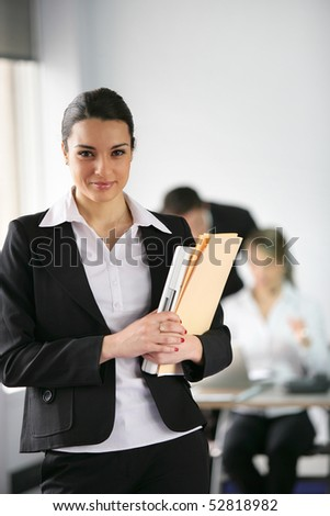 Portrait of a smiling woman holding documents - stock photo