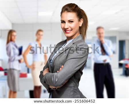 Portrait of a smiling woman in front of a group of business people - stock photo