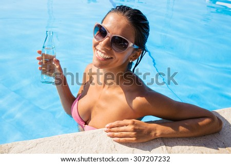 Portrait of a smiling woman in sunglasses standing in swim pool and holding bottle with water outdoors  - stock photo