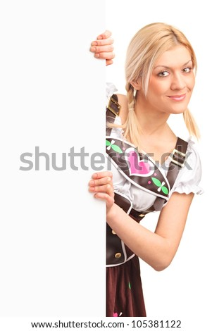 Portrait of a smiling woman in traditional bavarian costume holding a white panel isolated on white background