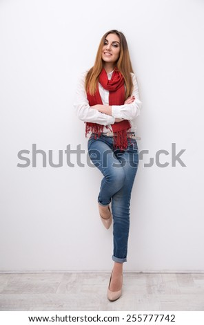 Portrait of a smiling woman leaning on the wall - stock photo