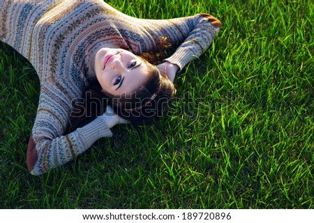 Portrait of a smiling woman lying on green grass - stock photo