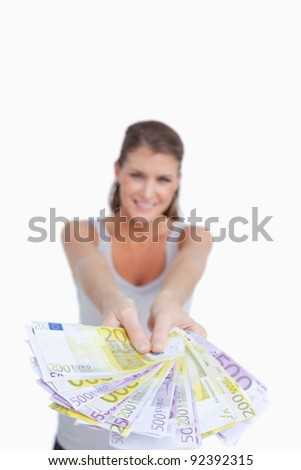 Portrait of a smiling woman showing bank notes against a white background - stock photo