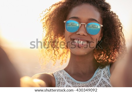 Portrait of a smiling woman wearing sunglasses at the beach - stock photo