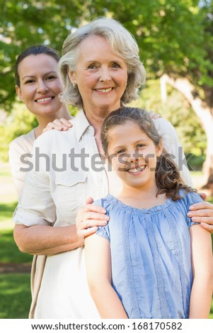 Portrait of a smiling woman with grandmother and granddaughter at the park - stock photo