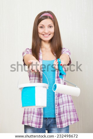 Portrait of a smiling woman with the paint roller and the bucket in her hands