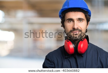 Portrait of a smiling worker in a construction site - stock photo