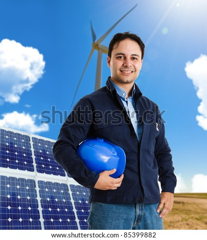 Portrait of a smiling worker in front of a wind power plant and a solar panel - stock photo