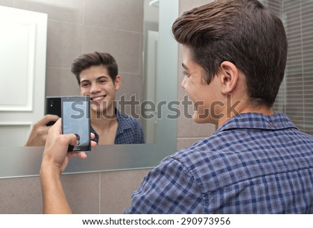 Portrait of a smiling young adolescent teenager man using a smartphone device to take selfies pictures of himself in a home bathroom mirror, networking in social media. Technology lifestyle at home. - stock photo