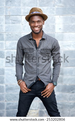 Portrait of a smiling young african american man with hat - stock photo
