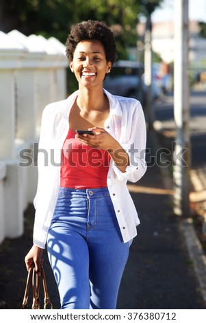 Portrait of a smiling young african lady walking along the street with mobile phone
