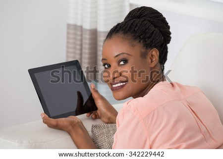 Portrait Of A Smiling Young African Woman Holding Digital Tablet