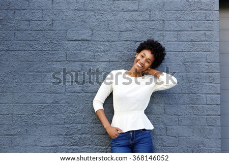Portrait of a smiling young african woman posing against gray wall - stock photo