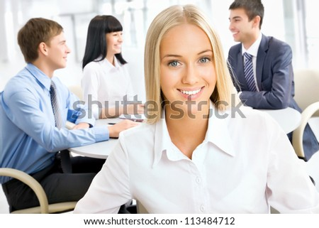 Portrait of a smiling young attractive business woman in a meeting . - stock photo