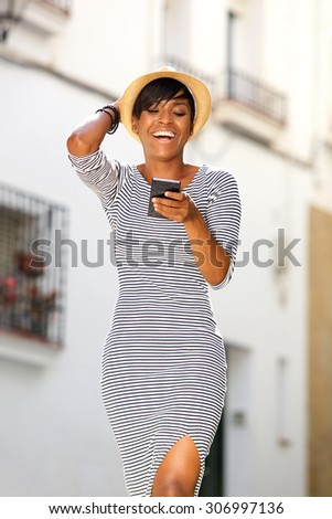 Portrait of a smiling young black woman reading text message on cell phone - stock photo