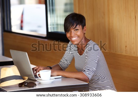 Portrait of a smiling young black woman using laptop - stock photo