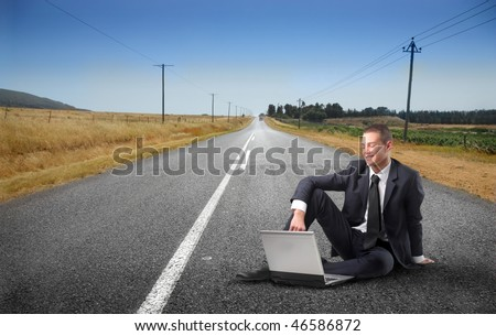 Portrait of a smiling young businessman sitting on a countryside road and using a laptop - stock photo